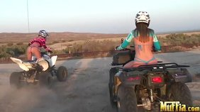Two adventurous lesbian girlfriends riding ATVs half-naked in the desert