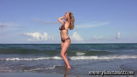 Bikini-clad and absolutely ravishing blonde posing on an empty beach