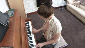 Playful-looking brunette with perky tits playing the piano topless