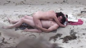 Dark-haired girlfriend riding her boyfriend's massive cock on the sand